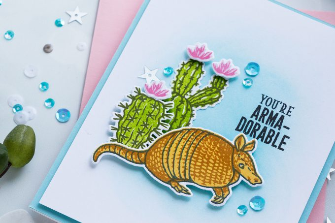 I used Soft Pool ink to blend a light blue background. Next, I foam mounted my armadillo stamped in Black, Butter Bar and Caramel and two cacti images stamped in Green Apple and Forever Green.